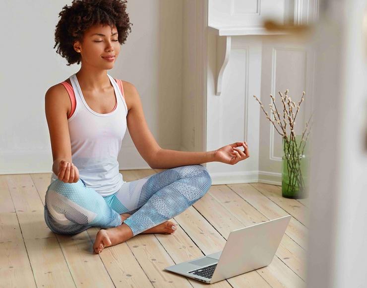 Femme méditant devant un ordinateur portable